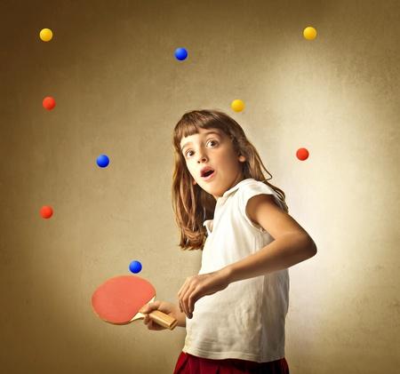 ping pong: Ni�a jugando ping pong con muchas bolas