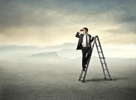 Hombre de negocios en una escalera con los prismáticos en un desierto