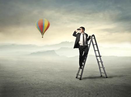 loin: Homme d'affaires sur une �chelle en utilisant des jumelles avec ballon � air chaud dans l'arri�re-plan Banque d'images