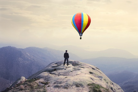 air baloon: Businessman on a peak with hot-air balloon in the background Stock Photo