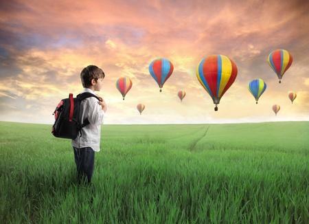 Kind einen Rucksack auf einer grünen Wiese mit Heißluftballons im Hintergrund
