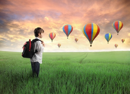 imaginacion: Ni�o que lleva una mochila en un prado verde con globos de aire caliente en el fondo Foto de archivo