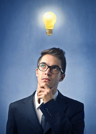 Young businessman with thoughtful expression and light bulb over his head Stock Photo - 10952155