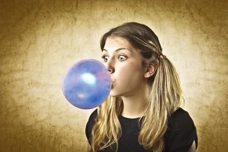 goma de mascar: Hermosa mujer haciendo una burbuja con una goma de mascar Foto de archivo