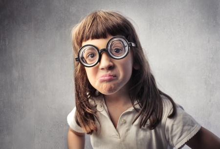 Angry little girl wearing thick eyeglasses photo