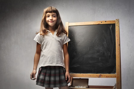 Smiling little girl standing beside a blackboard photo
