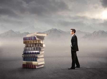 education success: Businessman standing beside a stack of books Stock Photo