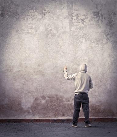 muro: Giovane scrittore in procinto di disegnare un graffito su un muro