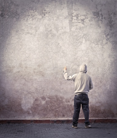 crack wall: Young writer about to draw a graffiti on a wall