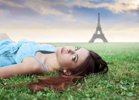 Beautiful woman lying on a green meadow with Eiffel Tower in the background photo
