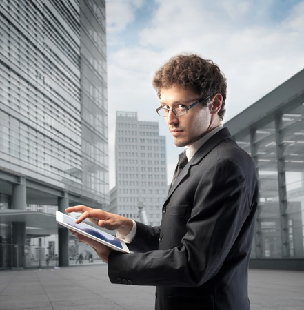 Young businessman using a tablet pc with office buildings in the background photo