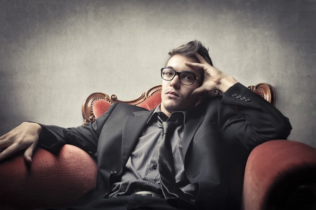 man with glasses: Handsome young man sitting on an armchair