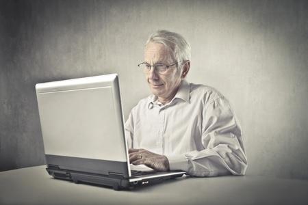Senior man using a laptop photo