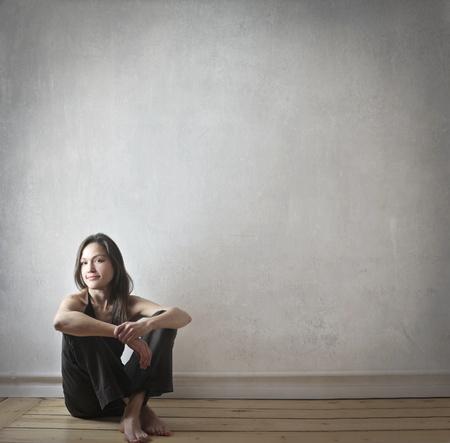 mujer sentada: Hermosa mujer sentada en el suelo en su casa Foto de archivo