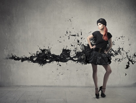 Elegant beautiful woman with her dress melting in black paint