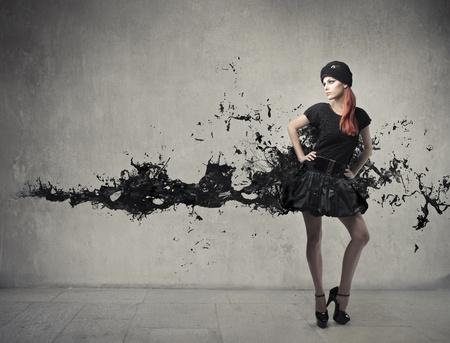 Elegante mooie vrouw met haar jurk smelten in zwarte verf
