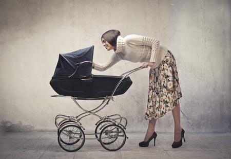 pram: Young mother cuddling her baby lying in a pram
