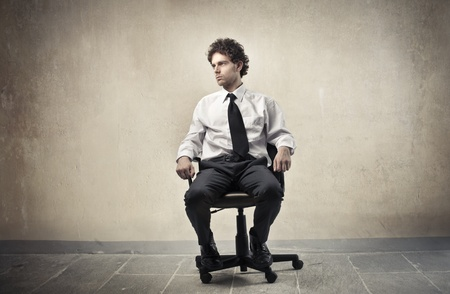 sitting on: Young businessman sitting on an office chair Stock Photo