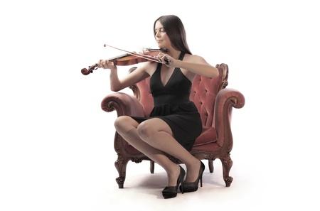 Hermosa mujer sentada en un sillón y tocar el violín Foto de archivo - 11102876