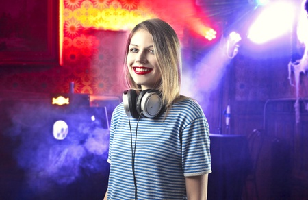 Smiling beautiful female deejay in a discotheque photo
