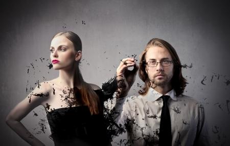Beautiful woman with fashion designer drawing her dress photo