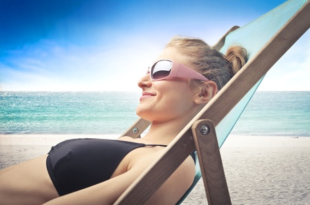 Smiling beautiful woman lying on a deckchair at the seaside photo
