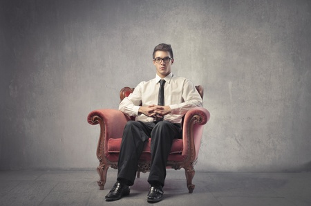 nobility: Young businessman sitting on an armchair