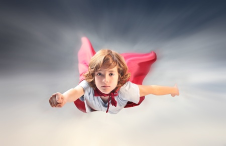 Child disguised as a superhero flying in the sky