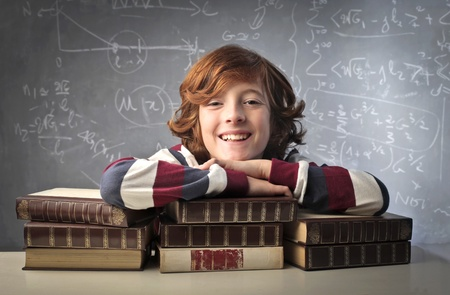 Smiling child resting on a stack of books in a classroom photo