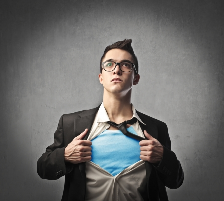 Businessman showing the superhero costume underneath his suit Stock Photo