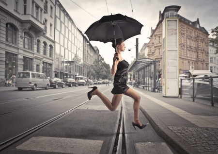 senda peatonal: Hermosa mujer elegante, se ejecuta bajo un paraguas en una calle de la ciudad