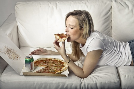 eating pizza: Young woman lying on a sofa and eating pizza Stock Photo