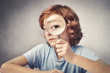 by see: Child looking through a magnifying glass