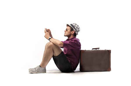 boy sitting: Young tourist sitting against a suitcase and using a mobile phone