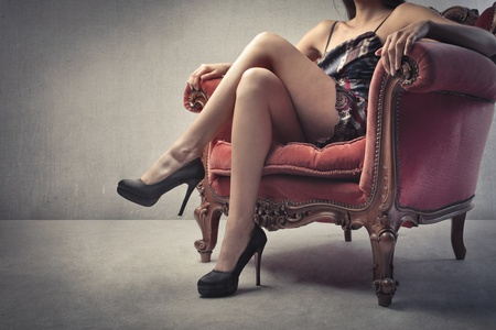 Closeup of a beautiful womans body sitting on an armchair photo