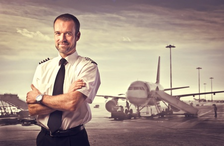 Smiling pilot with airplane in the background Stock Photo