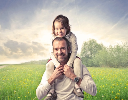 Smiling father carrying his daughter on his shoulders with green meadow in the background photo