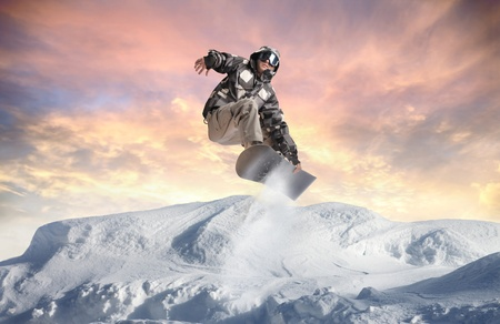 Young man snowboarding in the mountains photo
