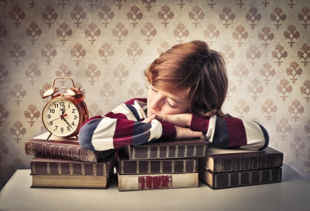 sleeping kid: Child sleeping on a stack of books beside an alarm clock