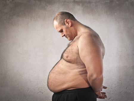belly fat: Sad fat man looking at his tummy Stock Photo