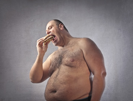 fat person: Fat man eating a hamburger Stock Photo