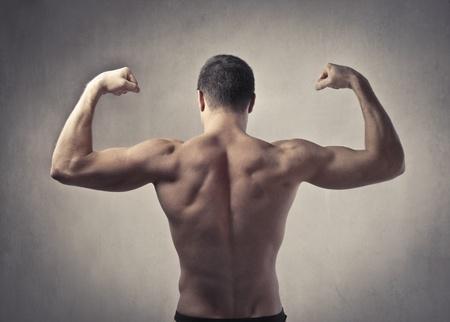 hombre fuerte: Vista trasera de un hombre fornido que muestra sus músculos