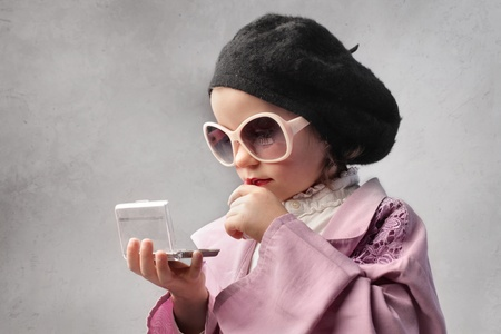 disguised: Little girl disguised as a woman looking at herself in a pocket mirror