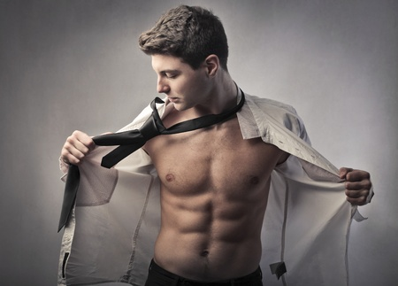 undress: Handsome young businessman putting on his shirt and tie