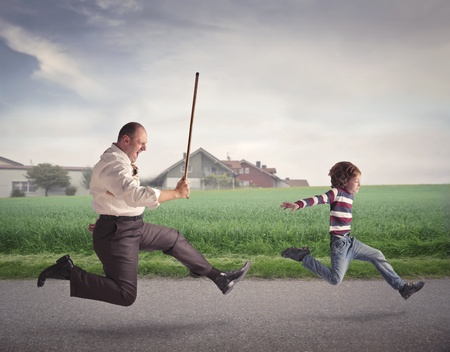 beating: Angry father running after his son with a stick Stock Photo