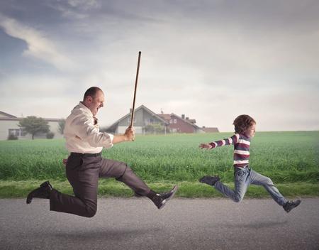 obedecer: Padre enojado corriendo detrás de su hijo con un palo