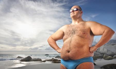 지방: 해변에서 뚱뚱한 남자 스톡 사진