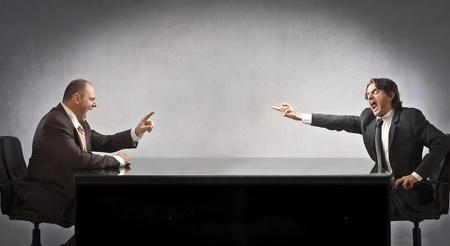 dialogo: Dos hombres de negocios sentado en una mesa y discutiendo