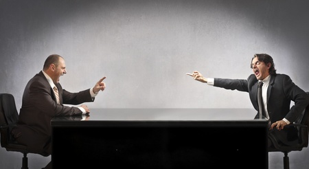 Twee zakenmannen zitten aan een tafel en ruzie