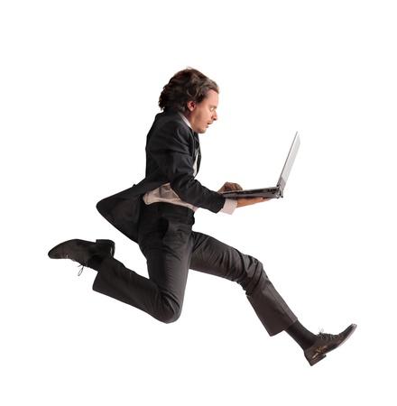 СПИД: Бизнесмен, работает быстро и проведение ноутбук Фото со стока